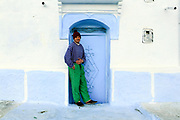 CHEFCHAOUEN, MOROCCO - 27th MARCH 2014 - Portrait of a local standing in a doorway in the Chefchaouen Medina - the blue city - Rif Mountains, Northern Morocco.