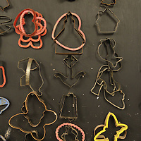 "A wall holds nearly all their ""cookie"" cutters they use to cut out different patterns."