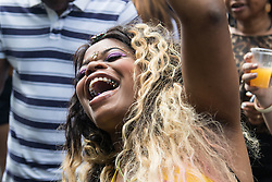 London, August 29th 2016. An exuberant woman dances at one of many sound systems during day two of Europe's biggest street party, the Notting Hill Carnival.