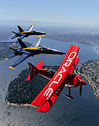 Aerobatic pilot Sean Tucker with his Team Oracle plane, flies in formation over Seattle. Blue Angel pilots LCDR Mark Tedro in #5 and Lt Ryan Chambertlain in #6.