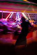 Young man swings manual powered carousel at local fair, neon lights at night