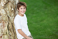 Smiling Boy Leaning Against Tree