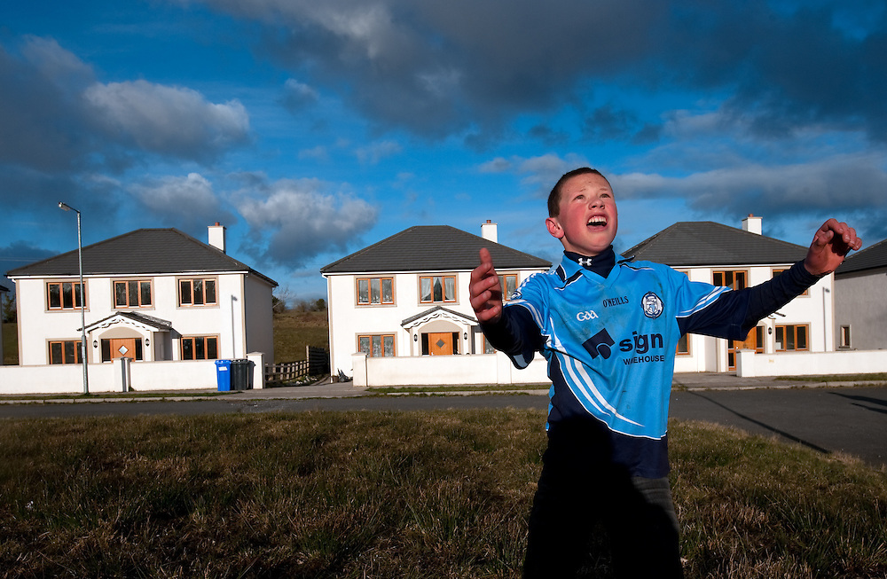 Jack Ozdobinski (12) plays football in a field in front of his house with the curtains in Drumshanbo, Co. Leitrim. Of the twelve exclusive detached houses in the development, only two are occupied.