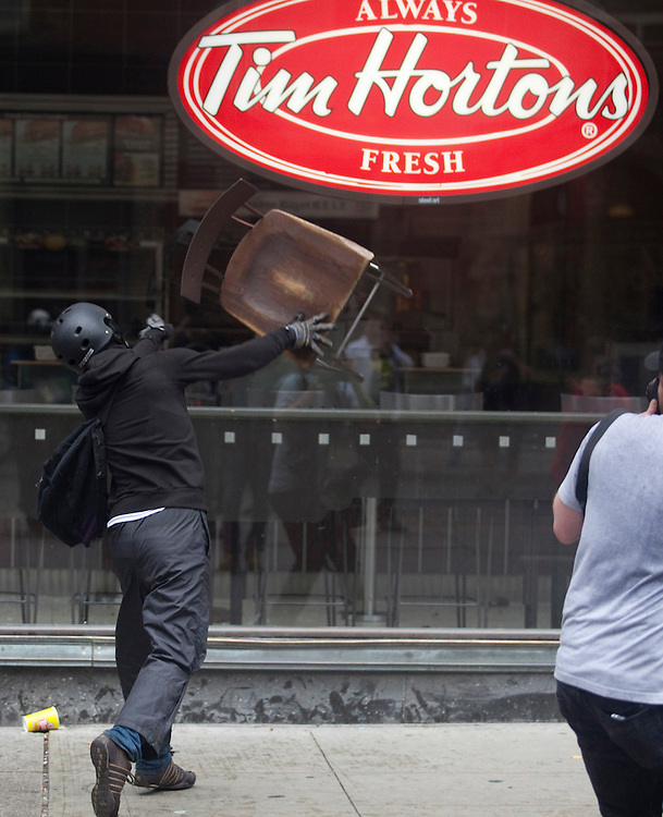 A protester tries to smashes a window in the Toronto's downtown core June 26, 2010 after a small group of anarchists broke from the main anti G20 demonstration and began a destructive march through the downtown.<br /> AFP/GEOFF ROBINS/STR
