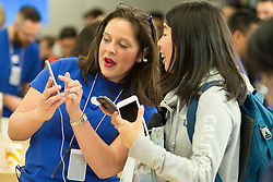 © Licensed to London News Pictures. 19/09/2014. An apple store employee shows a customer the new iphone 6 at the Apple Store in Chadstone Melbourne Australia. Australia is one of the first countries in the world to sell the iphone 6 due to geographic location & time zone. Photo credit : Asanka Brendon Ratnayake/LNP