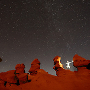 Jay Goodrich self portrait is photographed hiking in Goblin Valley State Park, Utah after sunset during night with stars.