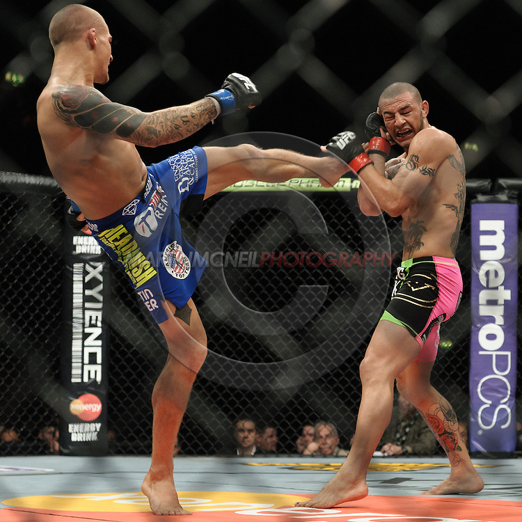 "LONDON, ENGLAND, FEBRUARY 16, 2013: Dustin Poirier (L) kicks at Cub Swanson during ""UFC on Fuel TV 7: Barao vs. McDonald"" inside Wembley Arena in Wembley, London on Saturday, February 16, 2013 (© Martin McNeil)"