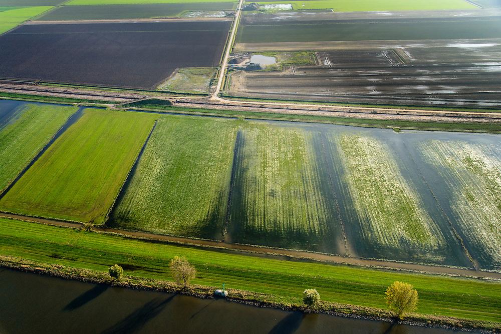 Nederland, Brabant, Gemeente Waspik, 28-10-2013; Overdiepsche polder: in het kader van het programma 'Ruimte voor de Rivier' (bescherming tegen hoogwater door rivierverruiming), is de zomerdijk langs de Bergsche Maas (met bomen) van instroomgaten voorzien, terwijl de winterdijk verlaagd wordt. De uiterwaarden zijn overstroomd, bij hoogwater kan de Overdiepse polder ook overstromen. De boerderijen in de polder zijn daarom gesloopt - de kale plekken - en verplaatst naar de dijk van het Oude Maasje (buiten beeld). De nieuwe boerderijen met bijgebouwen staan op terpen.<br /> Depoldering of Overdiep Polder, farms are relocated and built on mounds. This makes it possible for the river to overflow the polder in case of heigh waters. The dikes have been excavated.<br /> luchtfoto (toeslag op standard tarieven);<br /> aerial photo (additional fee required);<br /> copyright foto/photo Siebe Swart