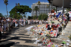 "People dressed in white gather around the make shift memorial as they attend a minute of silence held for the victims of the Bastille Day attack in the city of Nice, southeastern France, on August 07, 2016. Eighty-five people were killed and many were wounded after a jihadist ploughed a 19-tonne truck into a massive crowd celebrating Bastille Day, killing 85 people and wounding more than 400 others along the famous Promenade des Anglais during the July 14 celebrations. 85 balloons and 85 stars were stick in homage to 85 victims. A banner reading 'ce Putain de camion' (""Damn Truck"" - title is a French song, singer Renaud dedicated the song to his friend and fellow actor Coluche who died on 19 June 1986 in a motorbike accident with a truck between) Photo by Pierre Rousseau/Cit'images/ABACAPRESS.COM"