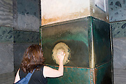 Turkey, Istanbul, Interior of the Hagia Sophia Museum female tourist at the Wishing Column AKA Sweating Column Model Release available