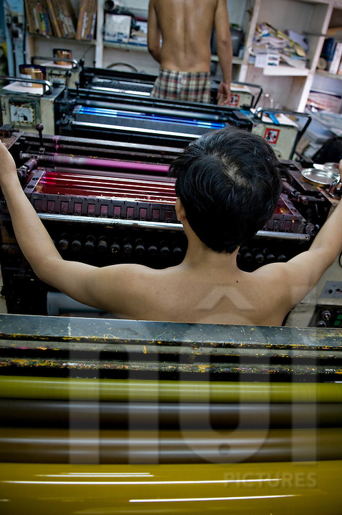 Two bare chested vietnamese print workers have some maintenance on ink-jet printers. Vietnam, Asia