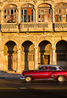 HAVANA, CUBA - CIRCA MAY 2016:  Classic American Card passing an old building of the Malecon in Havana, Cuba.