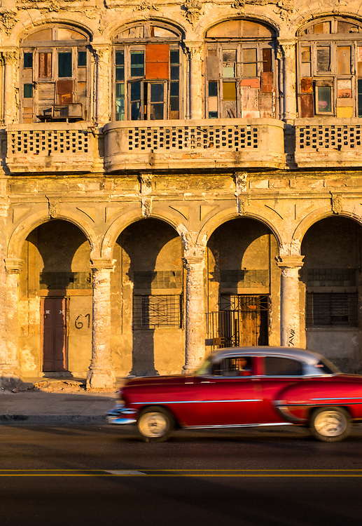 HAVANA, CUBA - CIRCA MAY 2016:  Classic American Card passing an old building of the Malecon in Havana, Cuba.