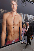 Elderly couple walk past a giant ad mural of a bare-chested young male model.