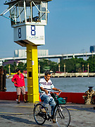 22 JANUARY 2019 - PHRA PRADAENG, SAMUT PRAKAN, THAILAND:  A passenger rides his bike off of a motorcycle and vehicle ferry that crosses the Chao Phraya River in Phra Pradaeng. The use of vehicle ferries across the river has gone down as the government has built bridges to connect communities on both sides of the river. The Phra Pradaeng ferries are the busiest vehicle ferries in the Bangkok metropolitan area. Since the BTS Skytrain now comes close to the ferry, the number of commuters going into Bangkok that use the ferry has increased.    PHOTO BY JACK KURTZ
