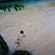 Children play in the Lanquin River, which has its source in the Grutas de Lanquin, or Lanquin Caves.  It is possible to float in a tube from the caves down river, getting out here, at El Retiro hostel.  Lanquin, Guatemala, July 2009.  (Photo/William Byrne Drumm)