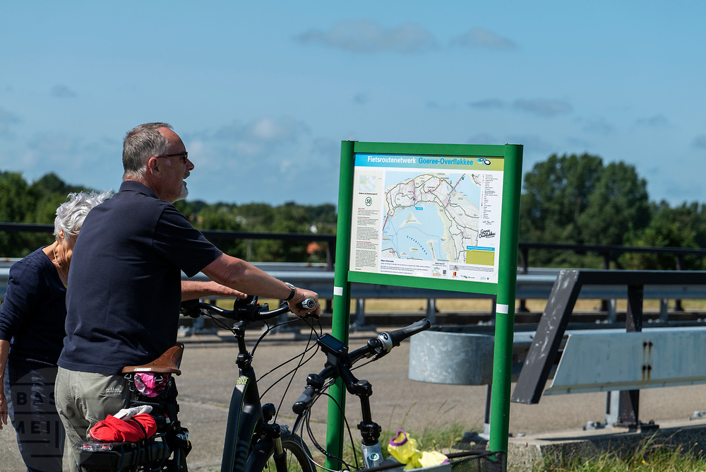 Fietsers bekijken bij Ouddorp de route op een bord van het fietsroutenetwerk.<br /> <br /> Cyclists study their route on a map near Ouddorp.