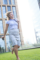 Happy businesswoman running at lawn in city