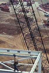 Construction worker walks steel beam on industrial building site.