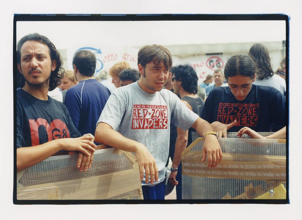 Proteste contro il summit del G8, Genova luglio 2001. 19 luglio. Tre manifestanti con scudi allo stadio Carlini. Nella pratica dei Disobbedienti, gli scudi, come altre protezioni, sono utilizzate per opporre resistenza passiva agli attacchi delle forze di polizia.