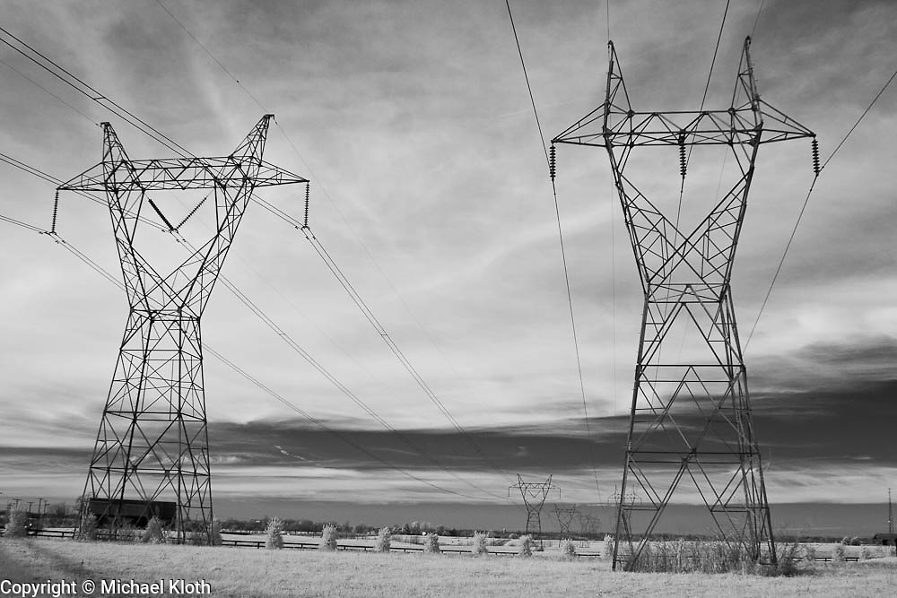 High voltage electrical power lines surrounded by a horse pasture in rural Kentucky.  Infrared (IR) photograph by fine art photographer Michael Kloth. Black and white infrared photographs