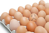 Sad face drawn on an egg surrounded by plain brown eggs in carton against white background