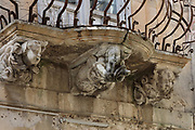 Sculpted figures of a horn player and 2 putti beneath 1 of the 8 balconies on the Baroque Palazzo la Rocca, built 1760-80 for the Baron of Sant'Ippolito, Don Saverio la Rocca, on Via Capitano Bocchieri in Ragusa Ibla, in Sicily, Italy. The town is split into the lower and older town of Ragusa Ibla, and the higher upper town of Ragusa Superiore, separated by the Valle dei Ponti. It is built on the site of an ancient city, inhabited by Sicels, Greeks, Carthaginians, Romans, Byzantines, Arabs and Normans. In 1693 it was devastated by an earthquake, and was rebuilt in the Baroque style. The town forms part of the Late Baroque Towns of the Val di Noto UNESCO World Heritage Site. Picture by Manuel Cohen
