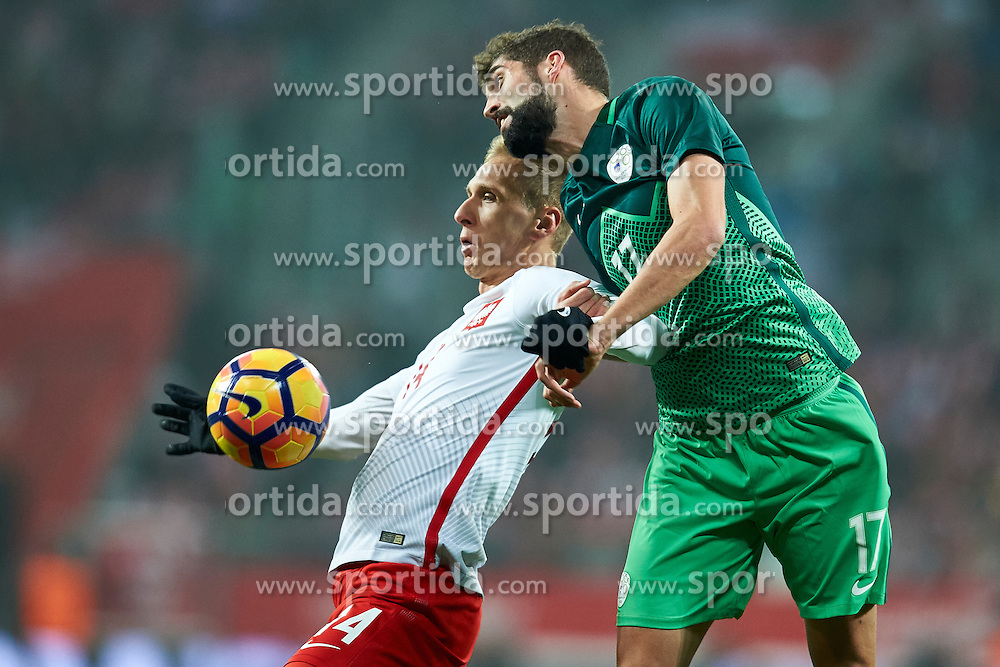 Wroclaw, Poland - 2016 November 14: Lukasz Teodorczyk of Poland fights for the ball with Miha Mevlja of Slovenia during Poland v Slovenia - International Friendly Soccer Match at Municipal Stadium on November 14, 2016 in Wroclaw, Poland.<br /> <br /> Adam Nurkiewicz declares that he has no rights to the image of people at the photographs of his authorship.<br /> <br /> Picture also available in RAW (NEF) or TIFF format on special request.<br /> <br /> Any editorial, commercial or promotional use requires written permission from the author of image.<br /> <br /> Mandatory credit:<br /> Photo by © Adam Nurkiewicz / Mediasport