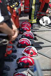 © Licensed to London News Pictures. 19/06/2017. London, UK. Members of the fire brigade place their helmets on the ground as they stand for a minutes silence for the victims of the Grenfell tower block fire. The blaze engulfed the 27-storey building killing dozens - with 34 people still in hospital, many of whom are in critical condition. Photo credit: Peter Macdiarmid/LNP