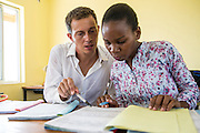 VSO volunteer Paul Jennings and local teacher Rebecca Ngovano sit at the back of a class monitoring another teacher during a geography class. After the assessment they provide feedback and support. Paul has been working with Rebecca for over 6 months to improve teaching methodologies in classrooms. Angaza school, Lindi, Tanzania
