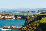 SANTANDER, SPAIN - April 17 2018 - Daytime coastal view over Santander seafront, Mataleñas Peninsula, Mataleñas municipal golf course and Magdalena Peninsula with mountain backdrop, Cantabria, Northern Spain, Europe.