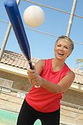 Senior woman hitting softball