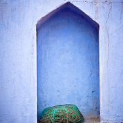 In a small alcove along the streets of old Delhi rests a green plastic  prayer cap.