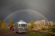 A double rainbow arcs over an Airstream travel trailer parked at a campsite near a rock formation in Vedauwoo, near Laramie, WY.