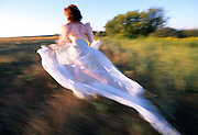 Woman in long white dress running through field