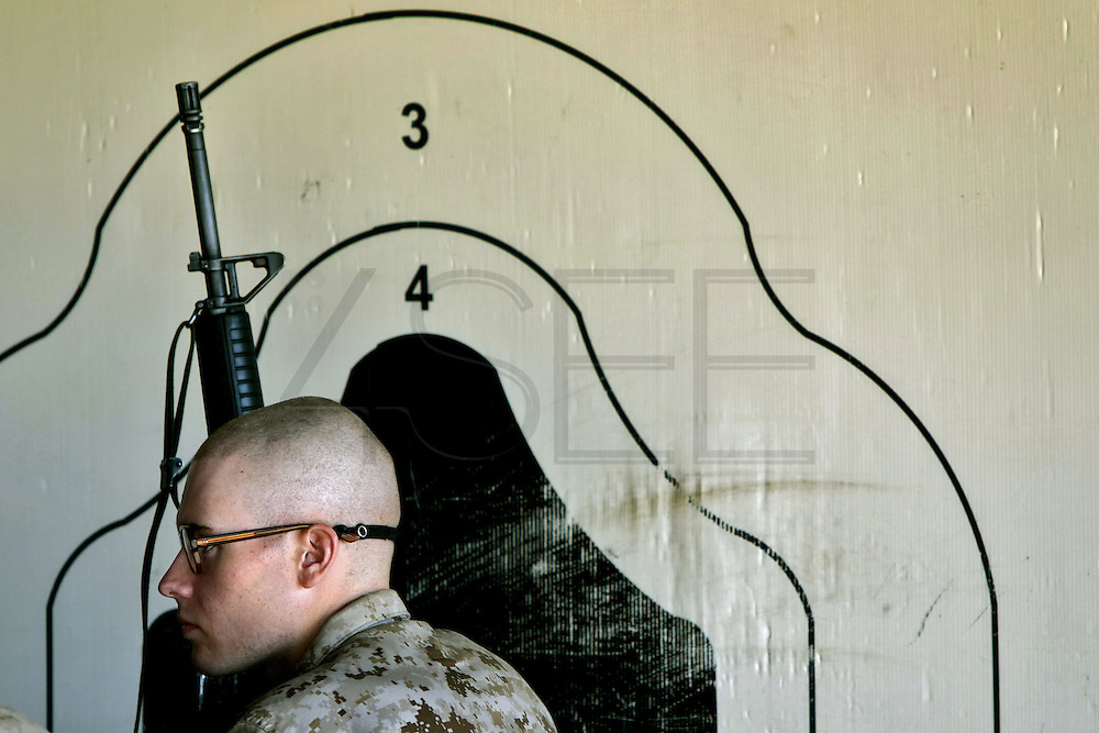 A large target is painted on the wall as a recruit listens intently to the instruction being given by a rifle instructor as they prepare to head out to the rifle range.  Marine Corps Recruit Depot at Parris Island in South Carolina is where all male recruits living east of the Mississippi River and all female recruits from all over the US receive their arduous twelve week training in their quest to become marines. Even though there are two current active wars and a weak economy, recruitment has not been effected.  Actually, recruiting numbers have increased, with more young men and women looking toward the military for answers.