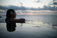 Beautiful woman with flower in her hair, looks out from an infity pool to the sunset over the ocean, Bali.