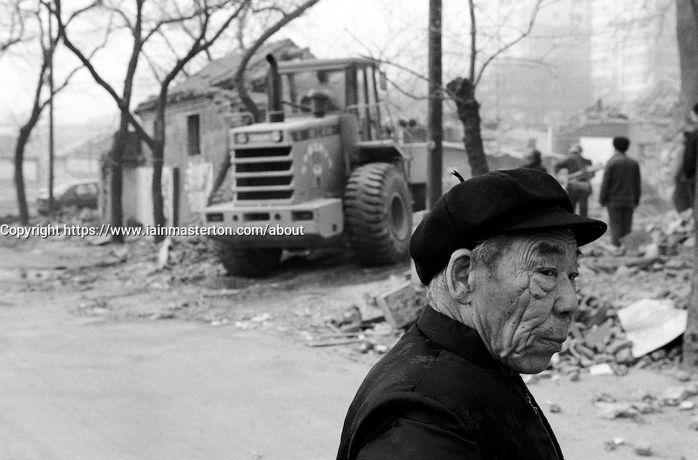 Elderly man watching the demolition of old traditional houses in a Beijing hutong