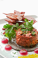 Chicken pibil timbale and tortilla chips,red onion spheres, habanero chile spheres on a bed of colado beans.