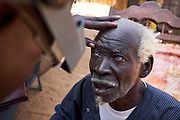 Trachoma grader Pierre Sarr examines the eyes of Mbaye Thiam, 96 years old in the village of Namzene Amar, K&eacute;b&eacute;mer Department, Senegal on February 23, 2017. Mbaye is the the final stages of trachoma, he has lost complete sight in one eye is almost blind in the other which has trichiasis. This eye can still be treated so that he does not lose his sight completely. <br /> <br /> Teams composed of Ministry of Health staff and RTI staff traveled to K&eacute;b&eacute;mer to carry out a trachoma surveillance survey. The activity includes household visits to assess the eyelids of community members to check for any signs of ongoing transmission of trachoma.  K&eacute;b&eacute;mer was previously considered endemic for trachoma, but a recent impact survey found that the prevalence was below 5%, meaning treatment is no longer required. This survey assesses if there is any recurrence of transmission, or if the districts is on track to eliminate the disease. <br /> <br /> Senegal is endemic for trachoma and is currently working to eliminate the disease by 2020. USAID&rsquo;s ENVISION Project, led by RTI International, is helping Senegal&rsquo;s Minist&egrave;re de la Sant&egrave; et de l&rsquo;Action Sociale (Ministry of Health and Social Work) to achieve this goal, providing support for trachoma activities.