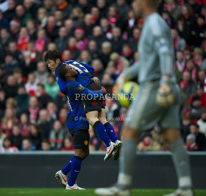 LIVERPOOL, ENGLAND - Saturday, January 28, 2012: Manchester United's goal scorer Ji-Sung Park is antagonistically carried towards the Kop by Patrice Evra after scoring the first equalising goal against Liverpool during the FA Cup 4th Round match at Anfield. (Pic by David Rawcliffe/Propaganda)