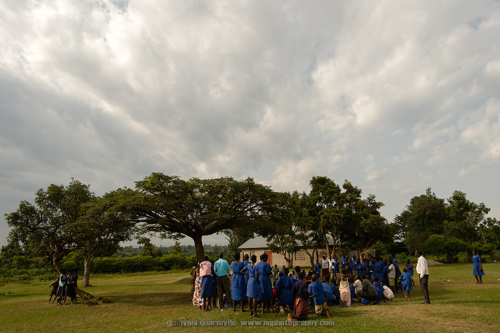 Students gather to watch a drama production dealing with a range of child welfare issues, including child marriages, domestic and sexual abuse, and menstrual hygiene management at Aputiri Primary School in Eastern Uganda on 31 July 2014 as part of a program sponsored by Plan International.
