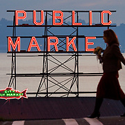 Woman carrying flowers crossing intersection at First and Pine with Pike Place Market sign and Elliott Bay behind her, Seattle, Washington