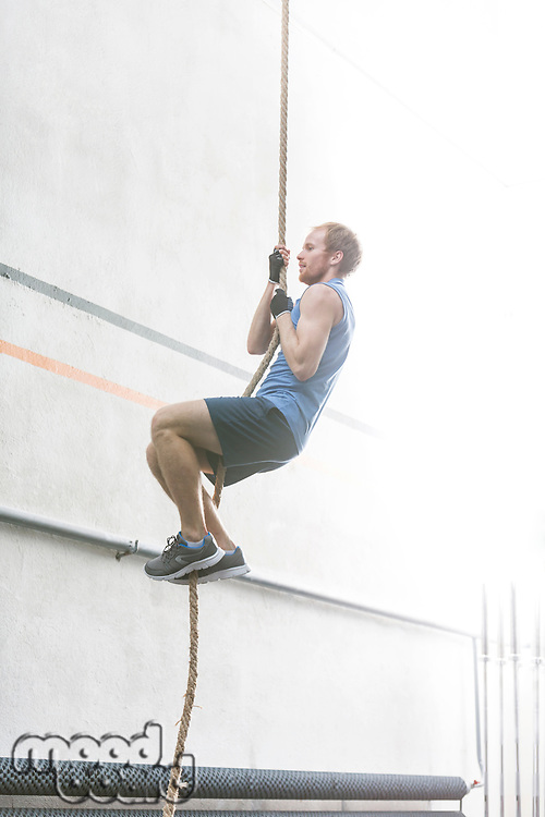 Side view of determined man climbing rope in crossfit gym