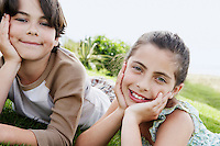 Pre-teen boy and girl reclining hands on chin on grass