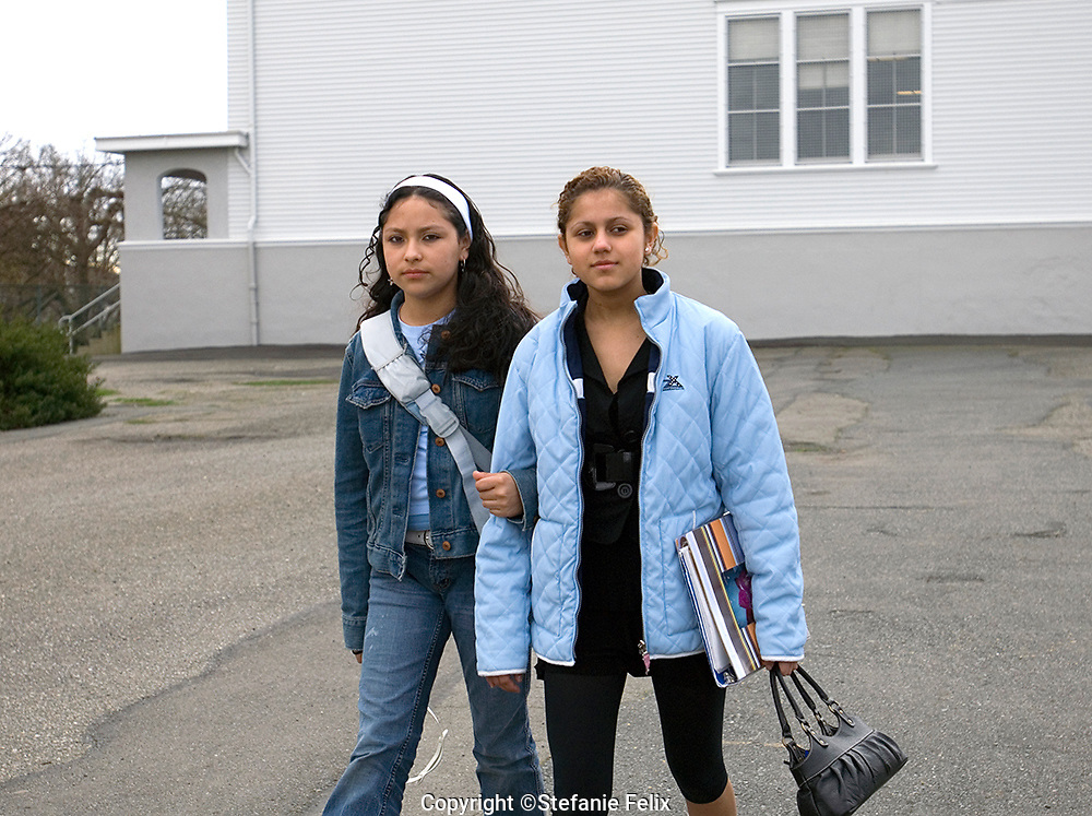Seattle, Washington: March 26, 2007.  Two secondary school Latina immigrant students walk across the school yard arm in arm.