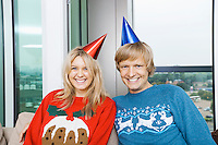 Portrait of cheerful couple wearing Christmas sweaters and party hats in living room at home
