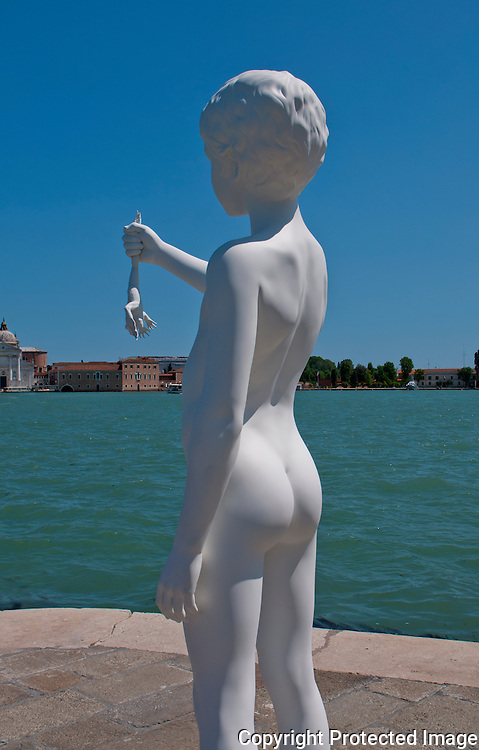 White statue of a nude youth holding a lizard seen in Venice, Italy against a beautiful blue sky.