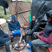 France. Refugees. Calais. So-called Jungle camp. Sudanese refugees try to keep warm