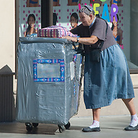 A homeless woman pushes her hand-made home along the Third Street Promenade on Friday, October 22, 2010.